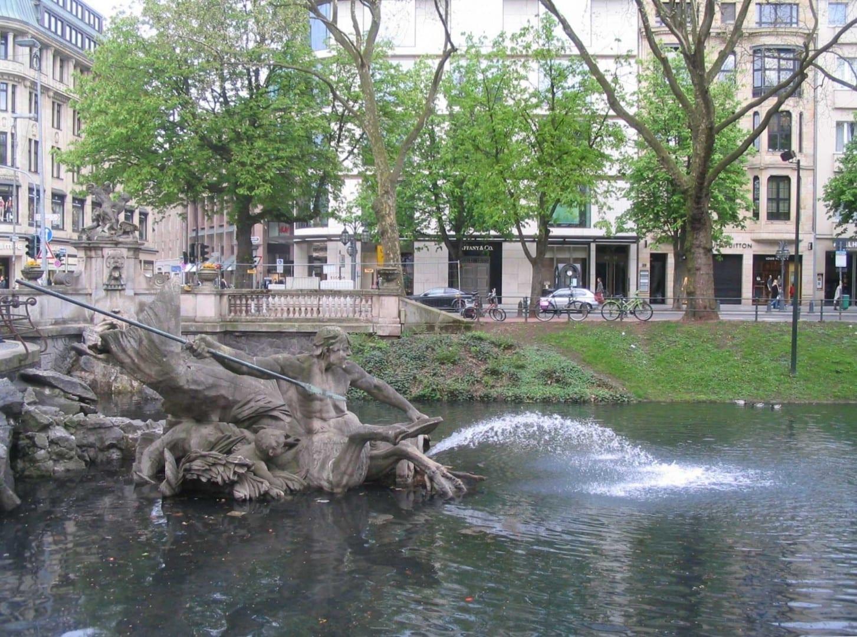 El extremo norte de la Königsallee con la fuente de Tritón Düsseldorf Alemania