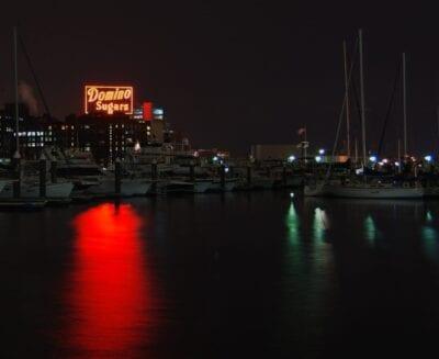 El símbolo de la clase trabajadora de Baltimore, la fábrica de azúcar de dominó en la noche a través del puerto... Baltimore Estados Unidos
