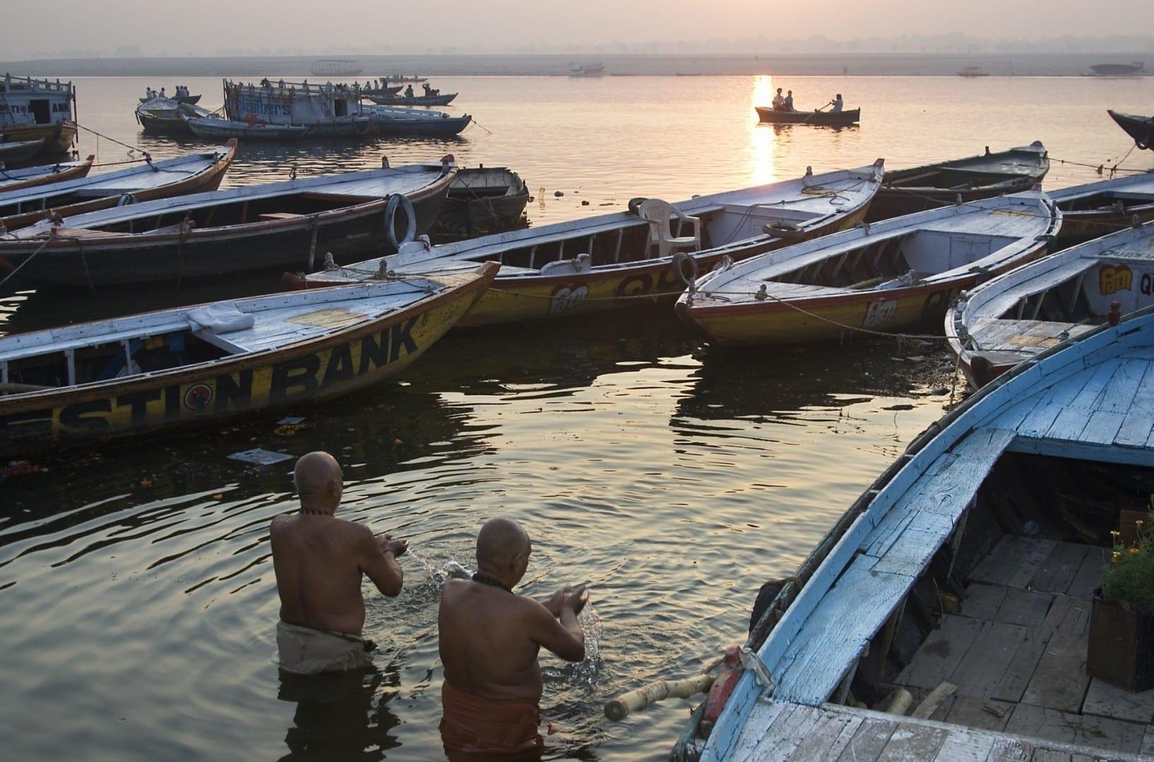 Hombres rezando entre los barcos en el Ganges Varanasi / Benares India