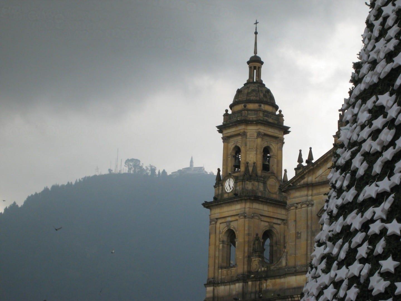 La torre del reloj de la Catedral Primada durante la Navidad, con el Santuario de Monserrate asomándose por encima Bogotá Colombia