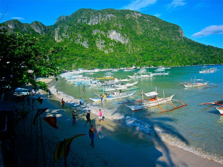 Largos barcos esperan a los pasajeros que saltan a la isla para explorar la Bahía de Bacuit El NIdo Filipinas