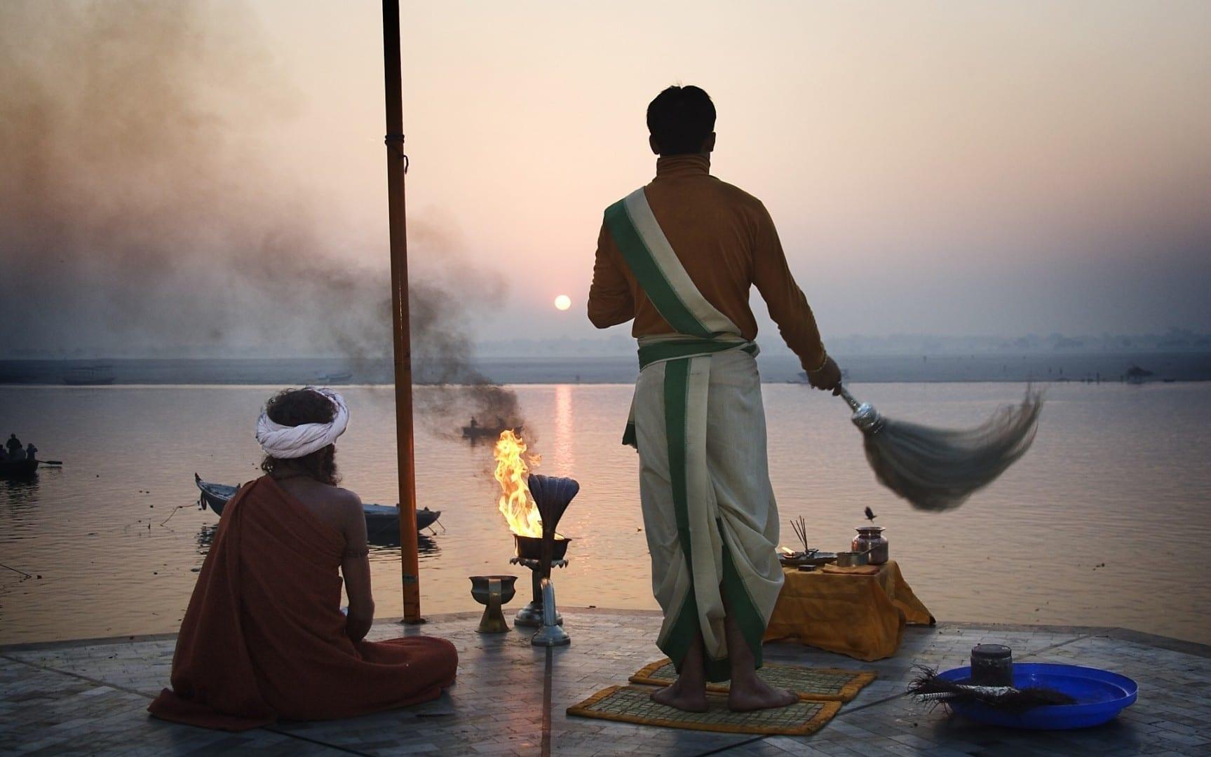 Sacerdote hindú saludando al sol en el Ganges Varanasi / Benares India