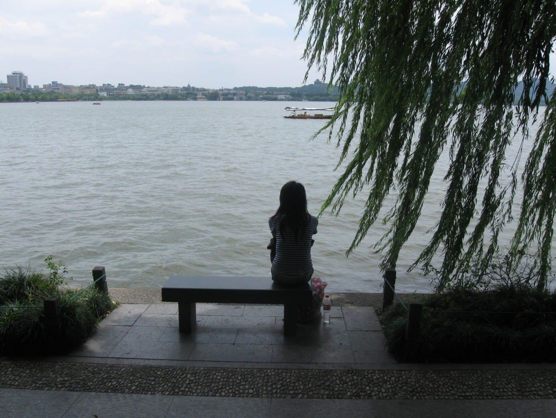 Sentado en un banco, con vistas al Lago Oeste Hangzhou China