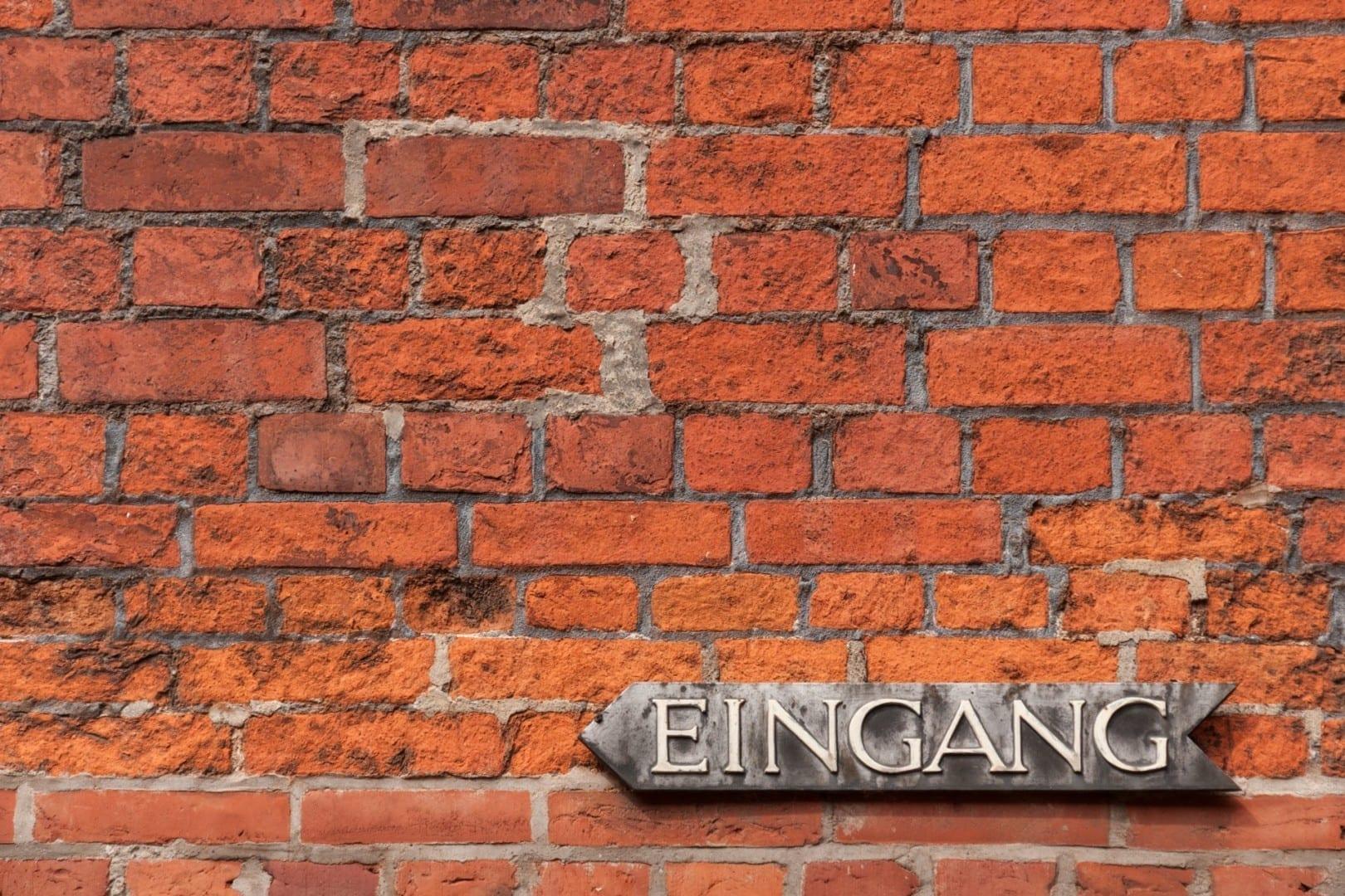 Un muro de ladrillos con un cartel de entrada en el Altstadt Lubeca Alemania