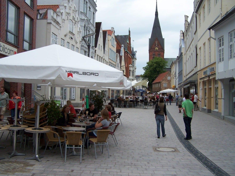 Ir de compras y comer en la calle peatonal Holm y Große Straße. En el fondo de la imagen está el San Marienchruch para ver. Flensburgo Alemania