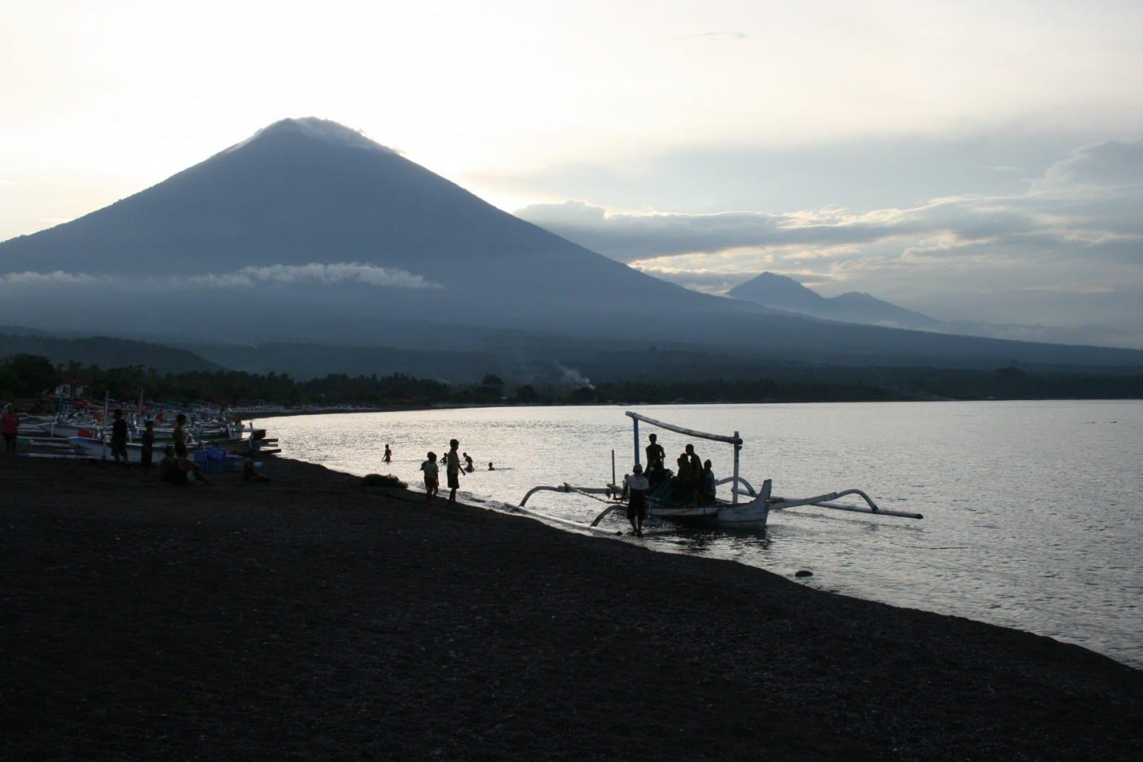 La playa de Amed con el sol desapareciendo detrás del Monte Agung Amed, Bali Indonesia