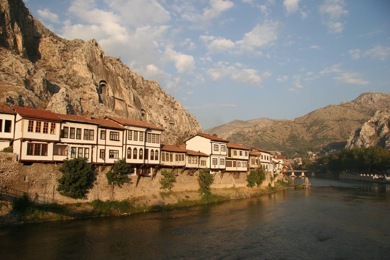 Las casas tradicionales de Amasya, a orillas del río, respaldadas por antiguas tumbas de roca Amasya Turquía