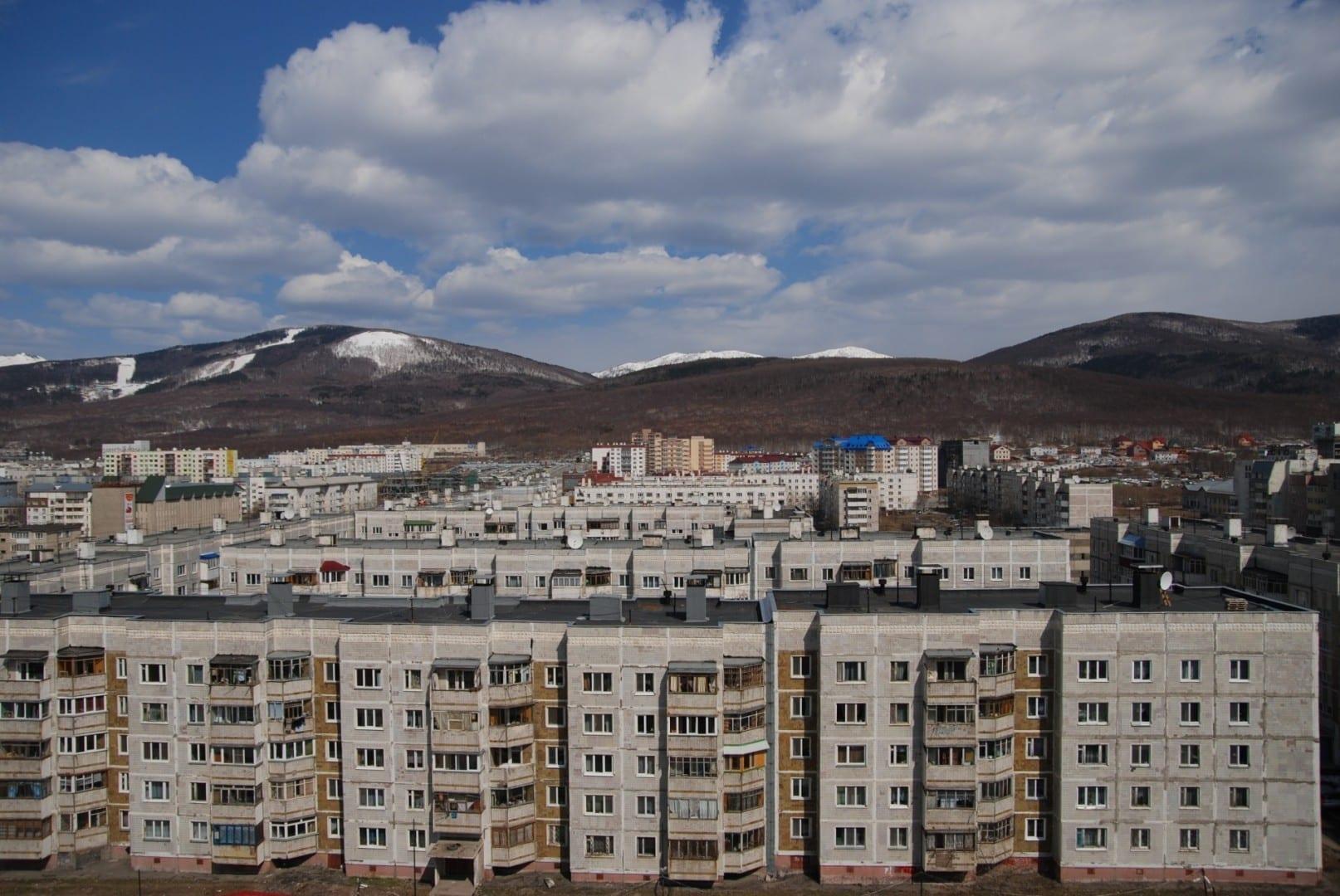 El paisaje típico de Yuzhno-Sakhalinsk: edificios de estilo soviético y montañas pintorescas Yuzhno-Sajalinsk Rusia