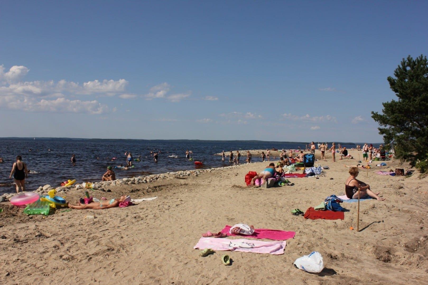 La gente que pasa el verano en un día caluroso en la playa de Paltaniemi... Kajaani Finlandia